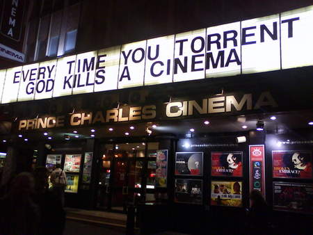 Photo of a cinema, that displays the message 'Every time you torrent, god kills a cinema'